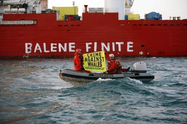 Handout picture of Greenpeace activists onboard inflatable boats displaying a banner in front the subsea vessel Far Samson