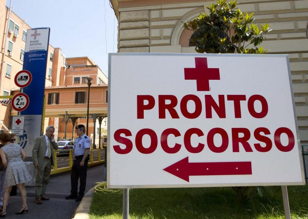 """Director Claudio Modini, head of the emergency room at the Policlinico Umberto I hospital, figure in a suit second from left, speaks on a mobile phone outside the emergency room (in Italian """"Pronto Soccorso"""") entrance of the hosptal, in Rome,Thursday June 20, 2013. Hospital officials said actor James Gandolfini, 51, died after suffering a cardiac arrest on Wednesday while vacationing in Rome. Modini, said Gandolfini arrived at the hospital at 10:40 p.m. (2040 GMT, 4:40 p.m. EDT) Wednesday and was pronounced dead at 11 p.m. after resuscitation efforts in the ambulance and hospital failed. (AP Photo/Alessandra Tarantino)"""
