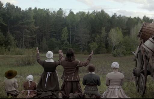 La preghiera della famiglia al momento dell'arrivo nella radura davanti alla foresta in The Witch (2015) di Robert Eggers