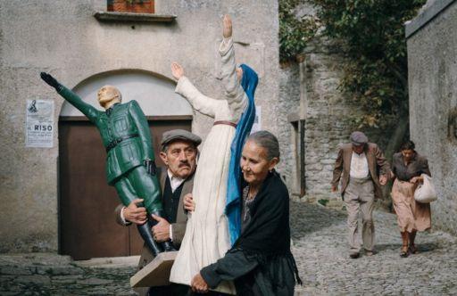 Zio Alfredo (Orazio Stracuzzi) e la vicina di casa (Aurora Quattrocchi) con le statue in gesso di Mussolini e della Madonna in una scena di In guerra per amore (2016)