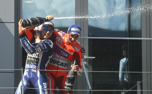 Spanish rider Jorge Lorenzo (L) sprays with Cava on Andrea Iannone of Italy during the podium celebration after the MOTOGP race at the Grand Prix of Austria in Spielberg on August 14, 2016. / AFP PHOTO / Michal Cizek