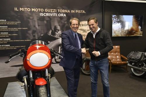 Giovanni Copioli FMI (a sinistra) con Davide Zanolini (Piaggio) alla presentazione del Trofeo. Alle loro spalle una gigantografia di Enrico Lorenzetti, campione mondiale nel 1952 sulla Guzzi 250