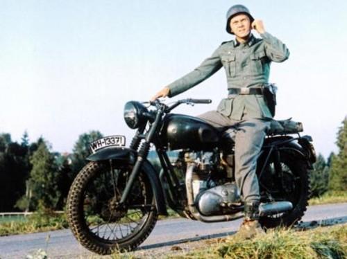 """IL TRUCCO. Steve Mc Queen nel film """"La grande fuga"""" del 1963. La moto non è militare, ma una Triumph abilmente camuffata. Il """"salto non sarebbe mai riuscito con un mezzo dell'epoca"""