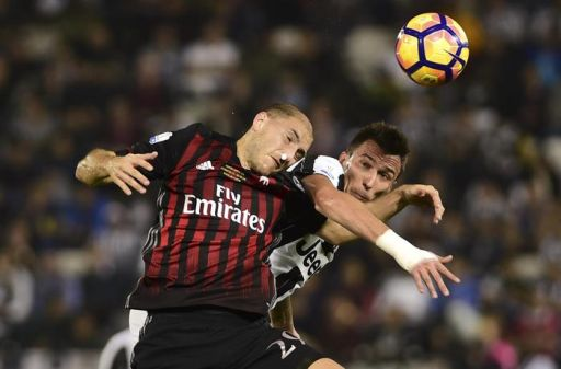 AC Milan's Gabriel Paletta, left, and Juventus's Mario Mandzukic vie for the ball during their Italian Super Cup soccer match, at the Al Sadd Sports Club in Doha, Qatar, Friday, Dec. 23, 2016. (ANSA/AP Photo/Alexandra Panagiotidou) [CopyrightNotice: Copyright 2016 The Associated Press. All rights reserved.]