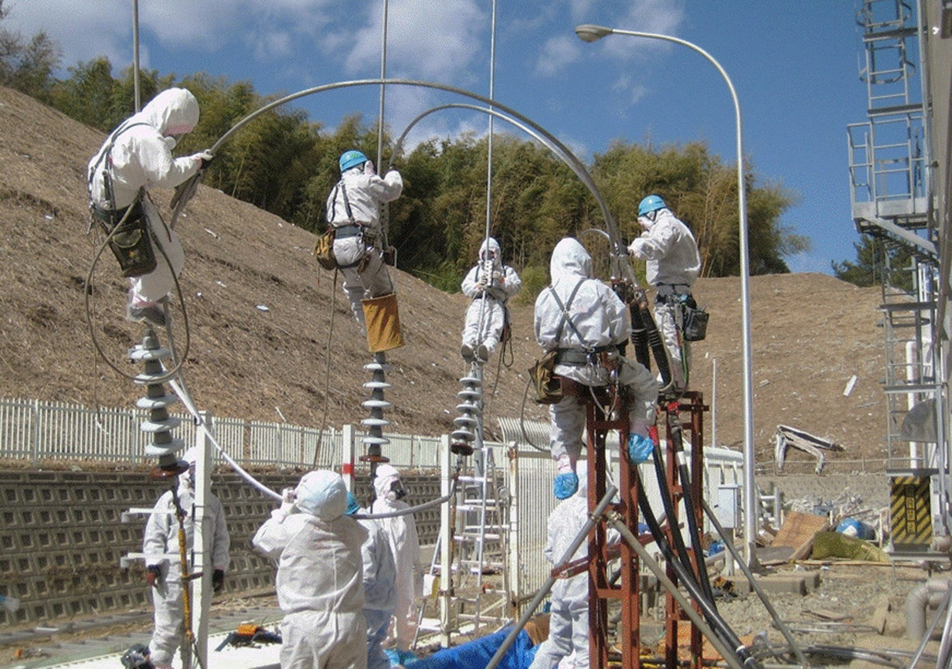 Handout file photo from Tokyo Electric Power Co. shows workers attempting to repair power lines at the Fukushima Daiichi Nuclear Power Plant in Tomioka