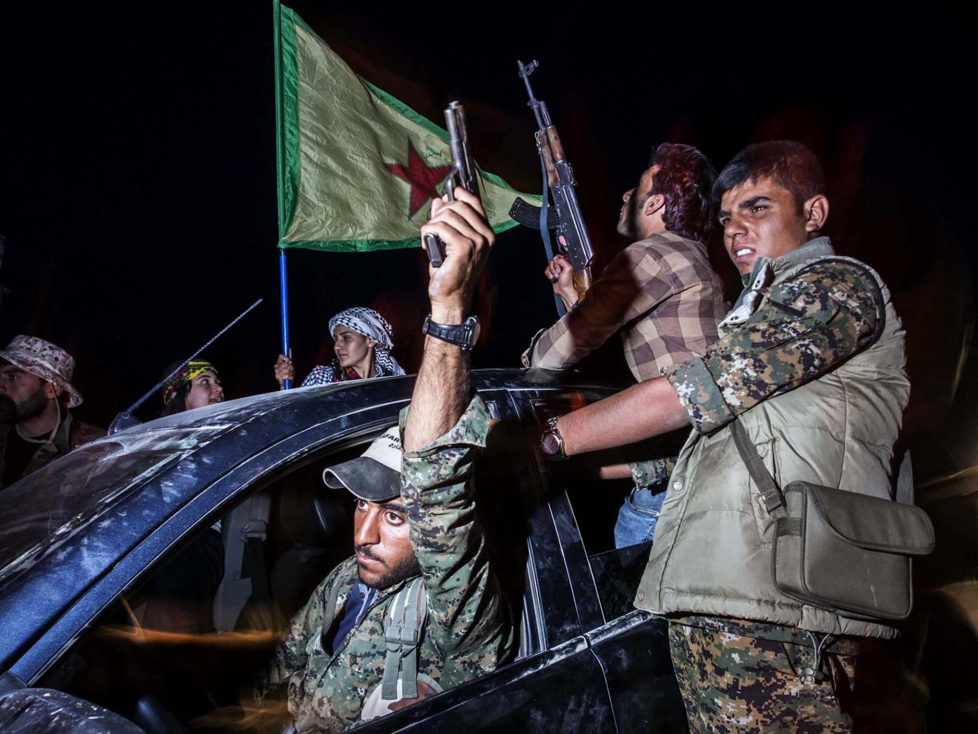 Siria.Kobane.15.6.15. Soldati appartenti allo YPG e YPJ entrano in trionfo nella cittá dopo aver  liberato la strada che unisce il cantone di Kobane con quello del Rojava tagliando in due l'autoproclamato stato islamico nel Kurdistan.