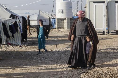 17/01/2015 -- Kirkuk, Iraq -- Suleiman Muhammad e suo nipote camminano di fronte alla loro tenda al campo di Laylan, Kirkuk
