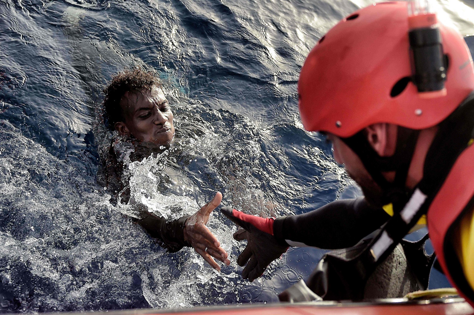 "TOPSHOT - A migrant is rescued from the mediteranean sea by a member of Proactiva Open Arms NGO some 20 nautical miles north of Libya on October 3, 2016.  Thousands of migrants are ""racing against the clock"" to make the perilous crossing from Libya to Europe before summer ends, with authorities in the conflict-torn country at a loss to stem the flow. / AFP PHOTO / ARIS MESSINIS"
