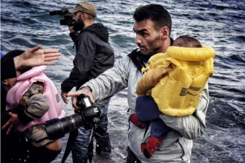 Aris Messinis tiene in braccio un bambino durante un'operazione di salvataggio a Lesbo, in Grecia (la foto, scattata da Petros Tsakamakis, è sul sito personale del fotografo)