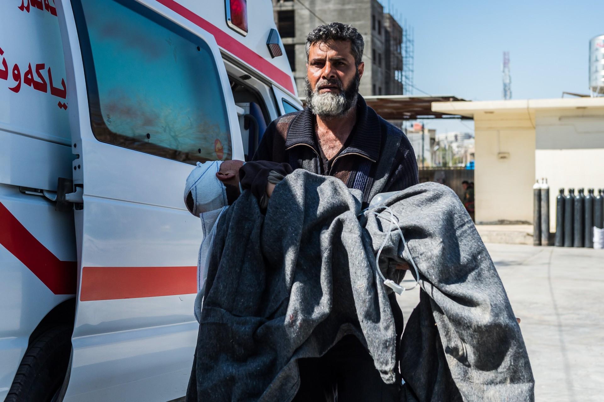8 Mar 2017 - Emergency Hospital Erbil, KRG IRAQ. Faraz Abdullah Shahab, 41 anni, porta il figlio Ahd presso il pronto soccorso medico dell'ospedale di Emergency di Erbil; il figlio e' stato ferito al volto dalle schegge di un'esplosione. Ha perso la moglie e 3 figli nella stessa esplosione. Faraz aveva un pissolo ristorante nel quartiere JAdida di Mosul.