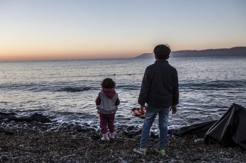 Two children stand on the shore in Lesvos and look out at the sea they just crossed in a rubber dinghy.