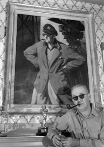 Il regista John Ford nel 1946. Nel quadro un'immagine del passato militare (da Wikimedia)