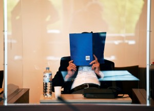 Bruno Dey, a former SS-watchman at the Stutthof concentration camp, hides his face behind a folder at the start of a hearing in his trial on July 23, 2020 in Hamburg, northern Germany. - The 93-year-old former Nazi concentration camp guard was handed a suspended sentence of two years in prison as a court in Hamburg found him guilty of complicity in WWII atrocities. In what could be one of the last such cases of surviving Nazi guards, Bruno Dey was convicted for his role in the killing of 5,230 people when he was a teenaged SS tower guard at the Stutthof camp near what was then Danzig, now Gdansk, in Poland. (Photo by FABIAN BIMMER / POOL / AFP)