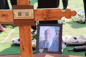 An image of George Bizos is seen next to his grave during the burial at the Westpark Cemetery in Johannesburg, South Africa, on September 17, 2020. - The late human rights lawyer and activist George Bizos represented Nelson Mandela during the Rivonia Trial. He was honoured with a special official funeral followed by a burial at Westpark Cemetery after passing away on September 9, 2020, at the age of 92. (Photo by KIM LUDBROOK / POOL / AFP)