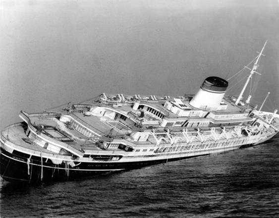 FILE - In this July 26, 1956 file photo, the Italian luxury liner Andrea Doria keels far over to starboard before sinking 225 feet to the bottom of the Atlantic 45 miles off Nantucket Island, Mass. Nearly six decades after the Andrea Doria slammed into another ocean liner, killing 46 people, explorers are preparing to do what 16 others have lost their lives attempting: get a fresh glimpse of the wreckage on the sea floor. Everett, Washington-based OceanGate will use a five-person submarine in June 2016 to get high-definition video and 3-D sonar images of the shipwreck. (ANSA/AP Photo/John Rooney, File) [CopyrightNotice: AP1956]
