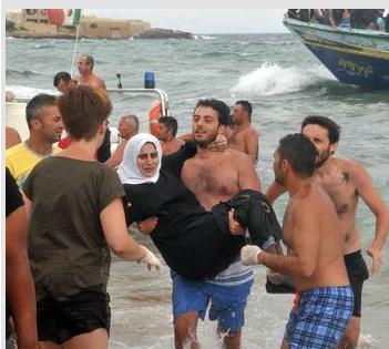 Un soccorritore che porta a braccia una donna araba a Morghella (Foto Ansa)