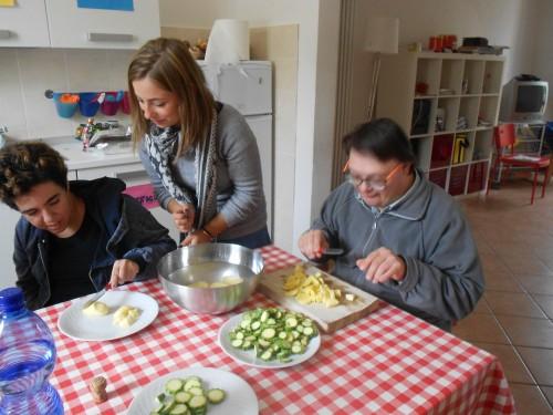 I ragazzi ospiti di Grassina con una educatrice che tagliano le verdure per pranzo