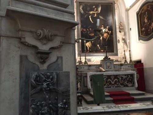 In primo piano l'ottava Misericordia, sullo sfondo il quadro del Caravaggio