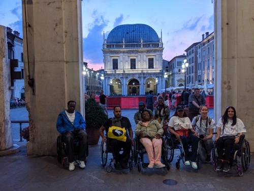 Il gruppo di persone con disabilita provenienti da New York sotto i portici di piazza della Loggia a Brescia