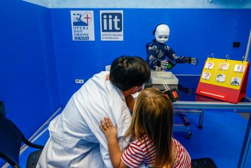Una bambina del Centro Boggiano Pico durante la terapia con iCub e la terapista