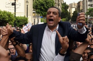 "(FILES) This file photo taken on May 4, 2016 shows the head of the Egyptian journalists union, Yahiya Kallash, demonstrating with journalists outside the Journalist Syndicate headquarters in Cairo. An Egyptian court on November 19, 2016, sentenced Kallash and two members of the journalists' union to two years in prison for ""harbouring fugitives"", allowing them to pay bail pending an appeal. The Egyptian Journalists Syndicate president, secretary general Gamal Abd el-Rahim and freedoms committee chief Khaled Elbalshy were charged in May with sheltering two journalists who were wanted for taking part in protests over the controversial transfer of two Red Sea islands to Saudi Arabia. / AFP PHOTO / MOHAMED EL-SHAHED"
