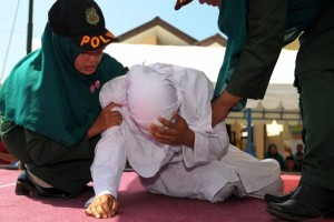 An Indonesian woman known as Linda (C) is helped by two Sharia officials after being caned for spending time in close proximity with a man who is not her husband, which is against Sharia law, in Banda Aceh on February 2, 2017. Aceh is the only province in the world's most populous Muslim-majority country that imposes sharia law. People can face floggings for a range of offences -- from gambling, to drinking alcohol, to gay sex. / AFP PHOTO / CHAIDEER MAHYUDDIN