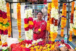 DPEBTC Indian woman selling flowers and garlands for hindu temple worship. Puttaparthi, Andhra Pradesh, India